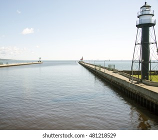 Two lighthouses at the end of piers looking out to Lake Superior guard the entrance of the Duluth harbor canal on a clear and calm morning.