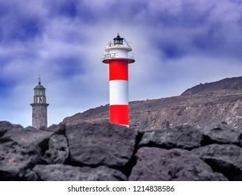 """two lighthouses, one old and one white-red striped and new on volcanic rock with blue-white sky. The sun is shining directly on the striped lighthouse. They are located in """"Fuencaliente"""", La Palma."""