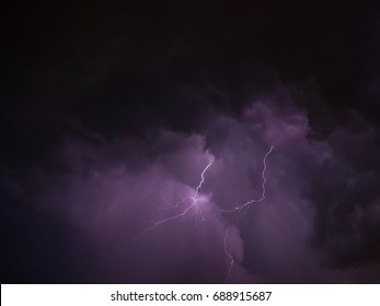 Two lightning and violet skies during thunderstorm in summer