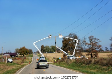 Two linemen stand in cherry pickers working on telephone lines in rural Arkansas.  Car has slowed to go around equipment.