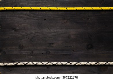 two lines of climbing rope on black wooden board. Photo frame has a lot of copy space