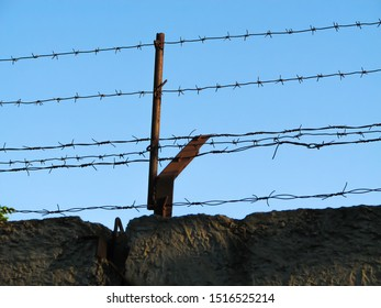 Two lines of rusty monobasic barbed wire and several lines of rusty dibasic barbed wire, stretched on rusty posts over an old concrete fence on a clear blue sky background