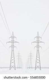 Two lines of transmission towers marching toward the horizon in a white winter scene, vertical crop