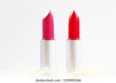 Two lipsticks, red and pink, placed over a white background giving sense of beauty.