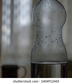 two liter bottle of water with drops and standing next to a mug close-up