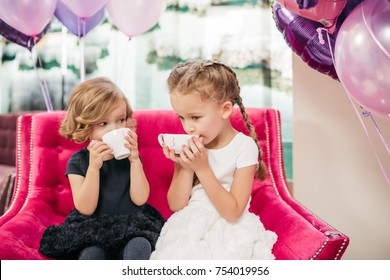 Two litle girls in black and white dresses drink tea sitting in a large pink chair
