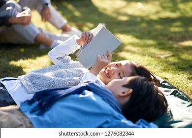 two little asian kids boy and girl lying on back on grass in park reading a book together with parents sitting in background.