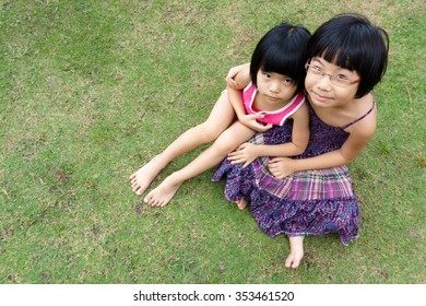 Two little Asian sisters sitting on green grass