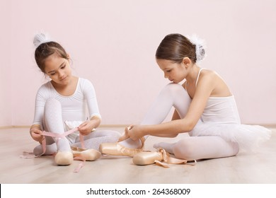 Two little ballerinas sitting on the floor and adjusting their ballet slippers. They are very cute
