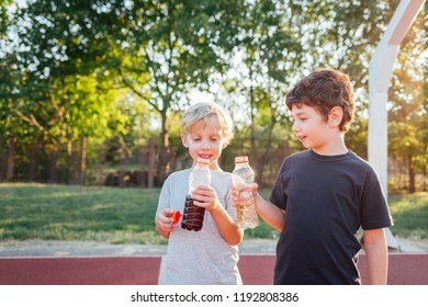 Two little basketball players drinking from bottles on a outdoors court.