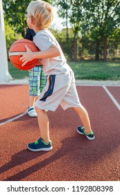 Two little basketball players training on a outdoors court.