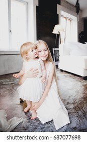Two little blond girls sisters in white dresses embrace in light interior room