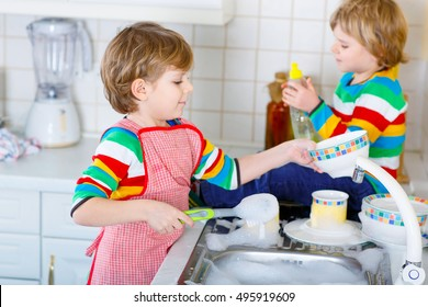 Two little blond kid boys washing dishes in domestic kitchen. Children, best friends having fun with helping with house work. Indoors, siblings in colorful clothes.