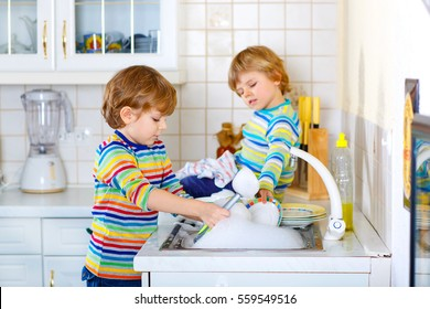 Two little blond kid boys washing dishes in domestic kitchen. Children, best friends having fun with helping with house work. Indoors, siblings in colorful clothes. Siblings learning different skills