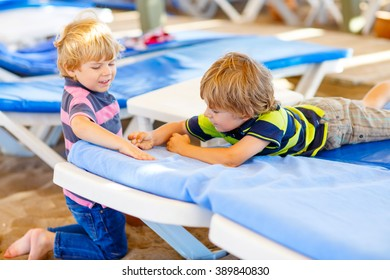 Two little blond kids boys building pebble stone castle on beach. Funny siblings, children playing with bucket and shovel. Vacations, summer, travel concept. Twins enjoying summer vacations on sea.
