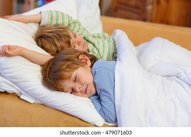 Two little blond sibling boys sleeping in bed. Tired kids dreaming and relaxing. Happy family of two brothers.