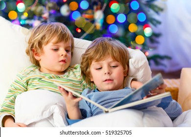 Two little blond sibling boys reading a book in bed near Christmas tree with lights and illumination. Happy family of two brothers, little twins and kids happy about gifts.