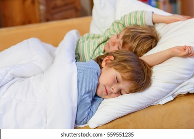 Two little blond sibling boys sleeping in bed. Tired kids dreaming and relaxing. Happy family of two brothers. Kids in colorful pajamas or nightwear.