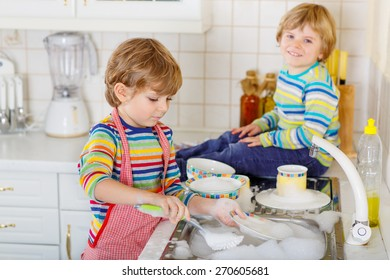 Two little blond twins boys washing dishes in domestic kitchen. Children having fun with helping with housework. Indoors, siblings in colorful clothes. Selective focus