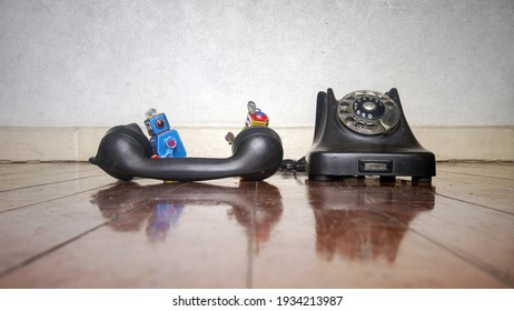 two little bots talking on an old vintage phone on a wooden floor