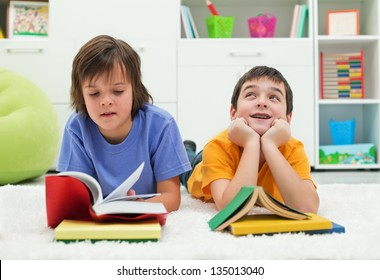 Two little boys with books, the one reading with  interest and the other dreaming looking up near the books