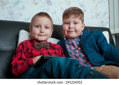 two little boys businessman with tablet isolated on a dark background