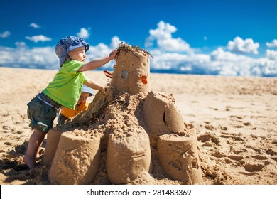 Two little boys in colorful t-shirts building large sandcastle on the beach