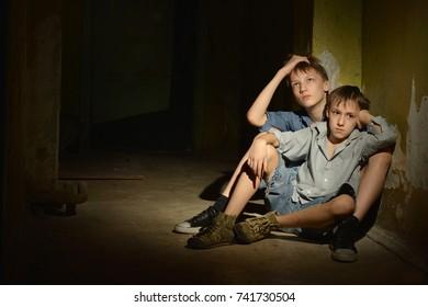 Two little boys in dark cellar