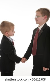 Two little boys dressed up in suits pretending to be businessmen and shaking hands. Isolated on white.