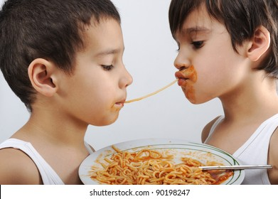 Two little boys eating spaghetti against each other