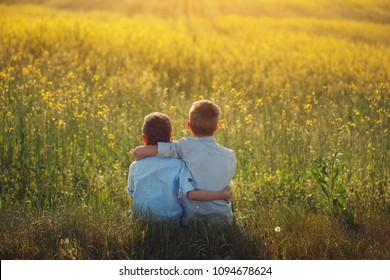 Two little boys friends holding around the shoulders in sunny summer day. Brother love. Concept friendship. Back view.