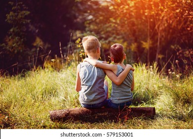 Two little boys friends hug each other in summer sunny day. Brother love. Concept friendship. Back view.
