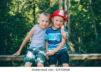 Two little boys friends sits outdoors in nature