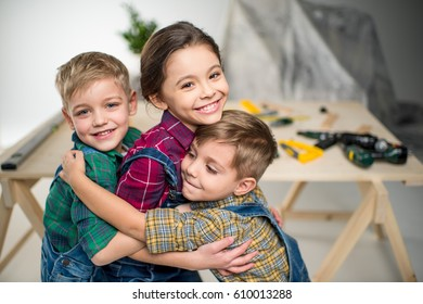 Two little boys and girl hugging in workshop and smiling at camera
