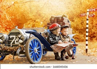 Zwei kleine Jungen in Gestalt eines Rennfahrers und eines Mechanikers in der Nähe eines alten Rennwagens in einem Herbstpark