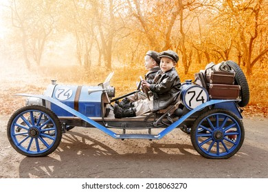 Two little boys in the guise of a racer and a mechanic riding an old race car in the autumn park