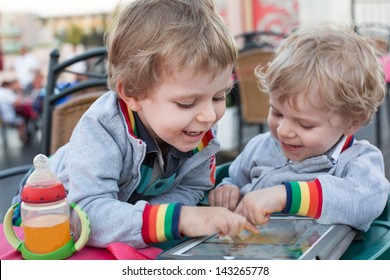 Two little boys having fun with tablet pc, outdoors