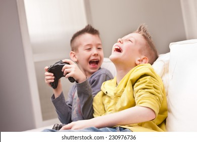 two little boys having lots of fun with video games