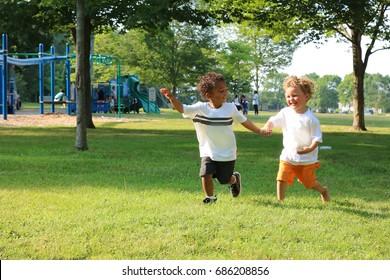 Two little boys are holding hands and running through the park.