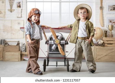 Two little boys imagine themselves as a pilot and a tourist and play near the plane in the room.