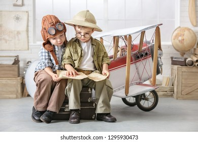 Two little boys imagine themselves as a pilot and a tourist and solve a map near the plane.