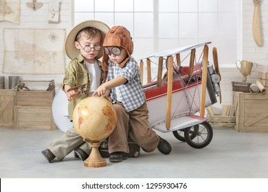 Two little boys imagine themselves as a pilot and a tourist and explore continents on a globe near an airplane.