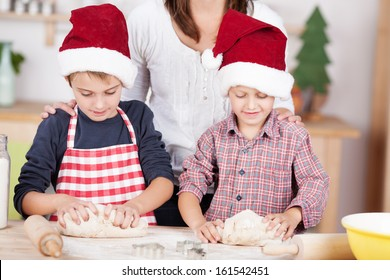 Two little boys learning to bake Christmas cookies watched by their mother as they stand at the counter in the kitchen in red Santa hats kneading the dough