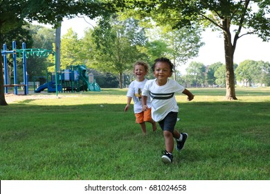 Two little boys, one white and the other African American, are running through a park together. Celebrate diversity, racism is taught concept.