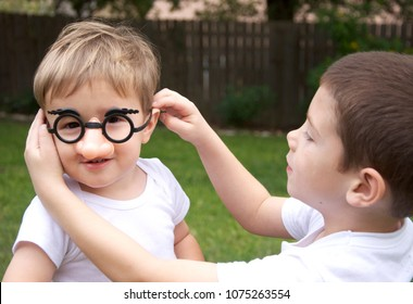 two little boys outisde, one disguised with silly glasses