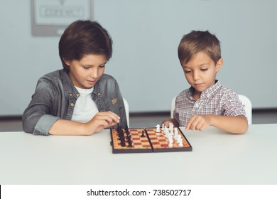 Two little boys play chess sitting at the table. On the chessboard are figures. Children are bored