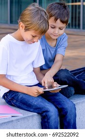 Two little boys playing with tablet computer outdoors