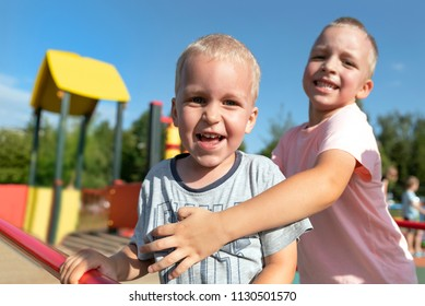 Two little boys playing together and having fun. Lifestyle family moment of siblings on playground.