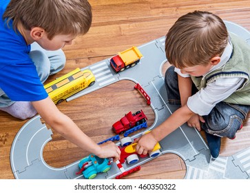 Two little boys plays with toy cars