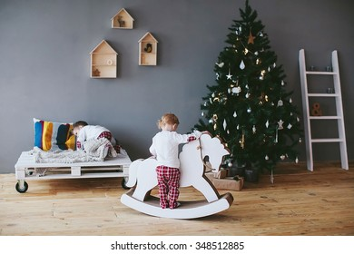 two little boys riding a horse in a christmas interior
